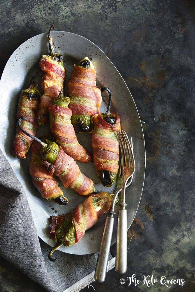 Keto Bacon-Wrapped Cheese-Stuffed Jalapeno Poppers on a silver tray with forks on a dark background