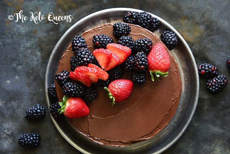 flourless chocolate cake with berries on top on a black background