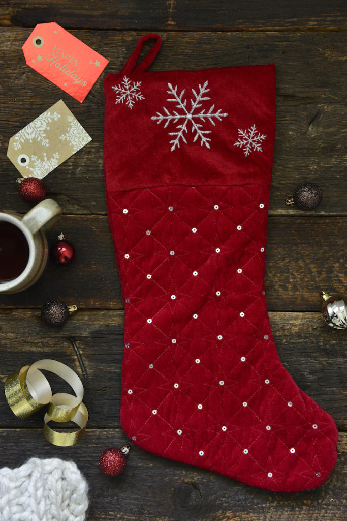 a black stocking on a dark board with tags and holiday themed