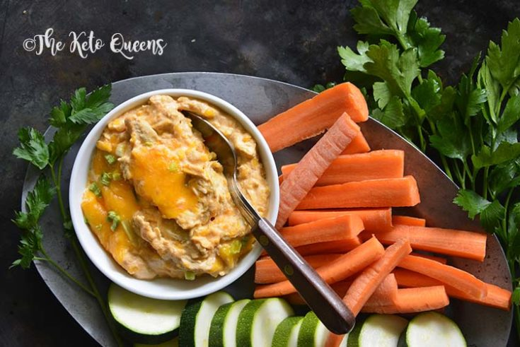 horizontal image of buffalo chicken dip in a small bowl with a spoon, with carrots, cucumber and cilantro