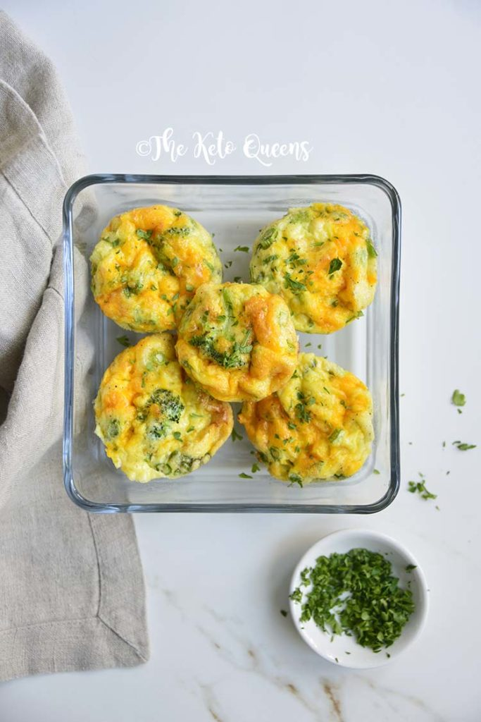 Overhead close up vertical image of broccoli and cheddar egg muffins in a glass storage container on a white background with parsley