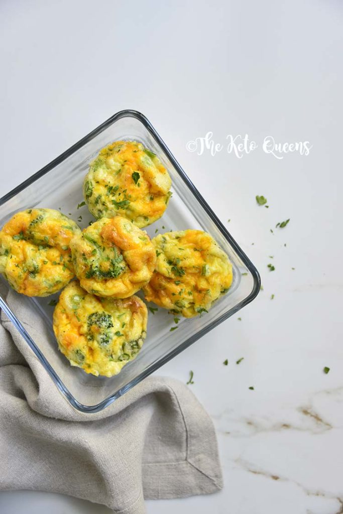Overhead close up vertical image of broccoli and cheddar egg muffins in a glass storage container on a white background