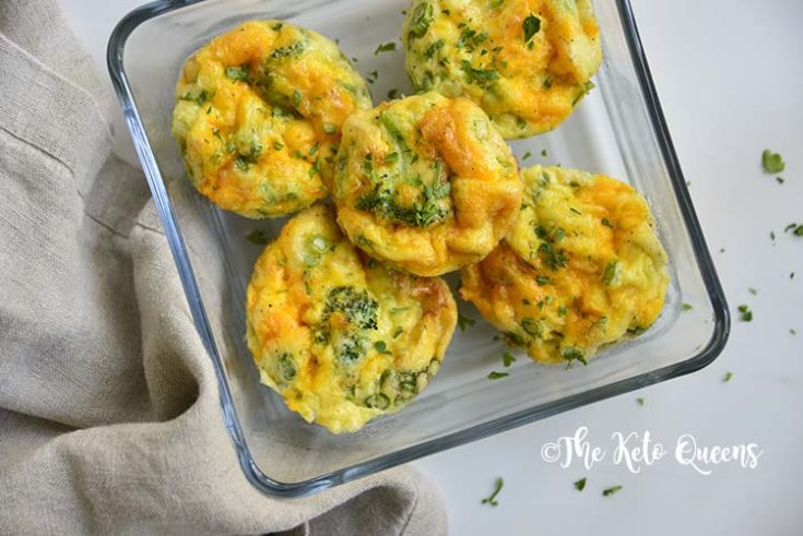 overhead horizontal image of broccoli and cheddar egg muffins in a glass storage container with a napkin