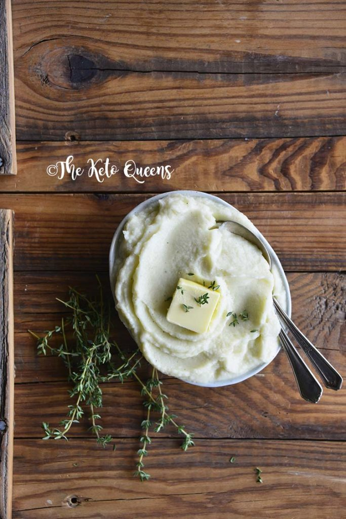 Vertical image from above of mashed cauliflower with fresh thyme and butter in a bowl with 2 spoons