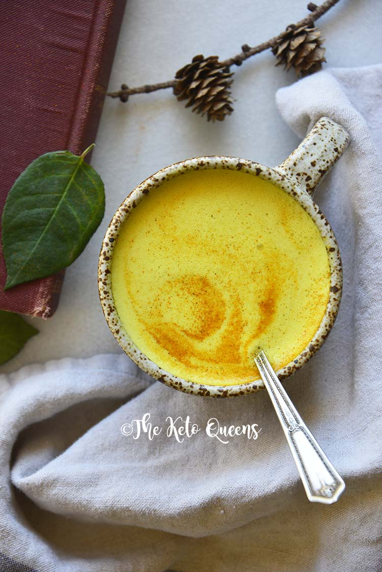 Top View of Golden Milk on Marble Counter with Red Book
