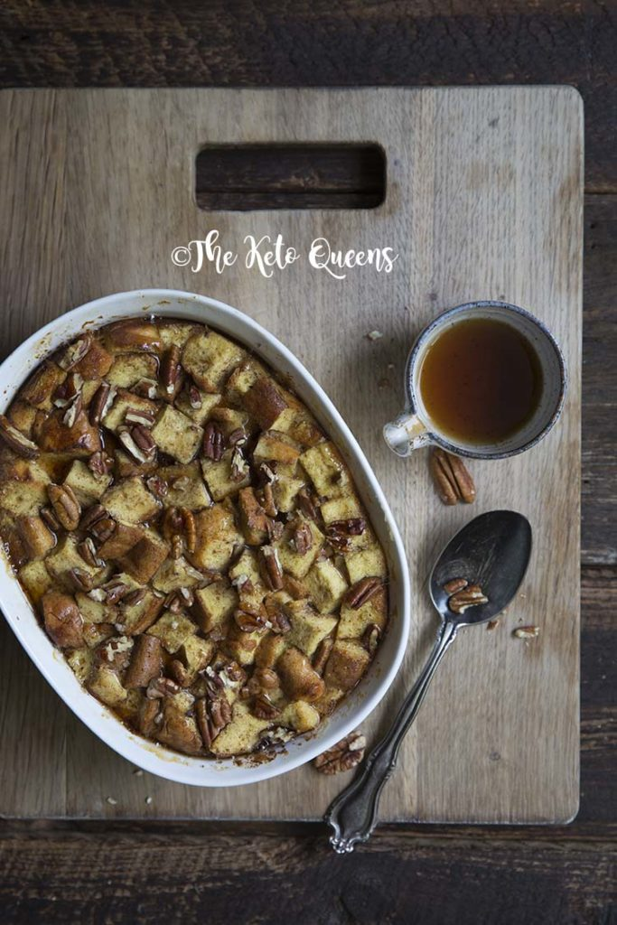 overhead vertical image of maple pecan french toast casserole in a white casserole dish, with a spoon and low carb syrup on a wood background