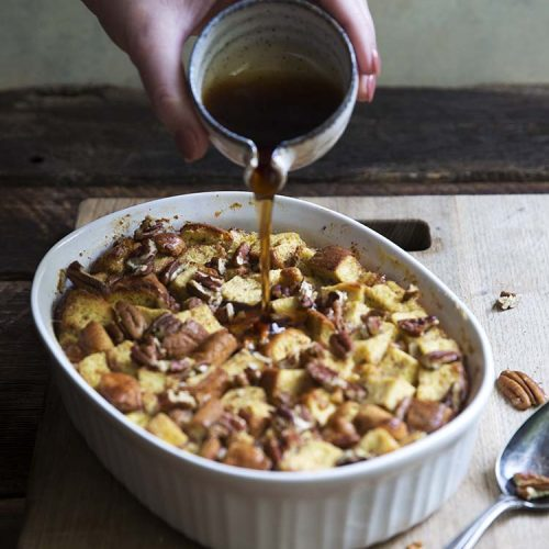 vertical image of maple pecan french toast casserole in a white casserole dish, with a spoon on a wood background with low carb syrup being poured onto it