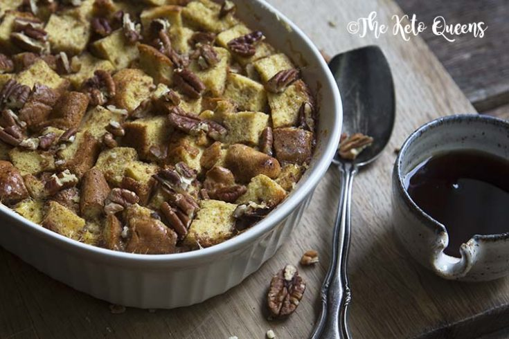 horizontal image of maple pecan french toast casserole in a white casserole dish, with a spoon and low carb syrup on a wood background