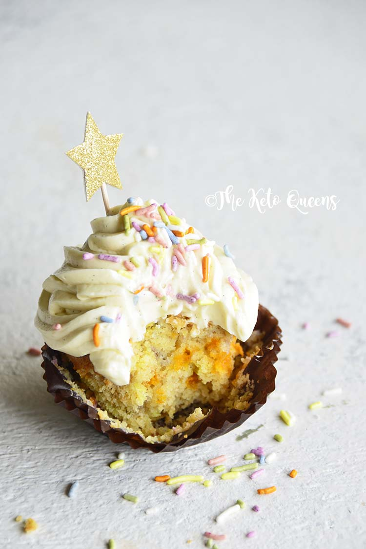 vertical image of a keto vanilla cupcake with white chocolate buttercream frosting with sprinkles and a star with a bite taken out of it