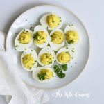 Vertical Image of a bunch of keto Instant Pot Deviled Eggs with Relish on a white plate with a white background with parsley on top