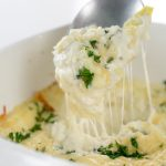 square image of Baked Creamy garlic parmesan hot artichoke dip in a white square casserole dish with a silver spoon taking a scoop