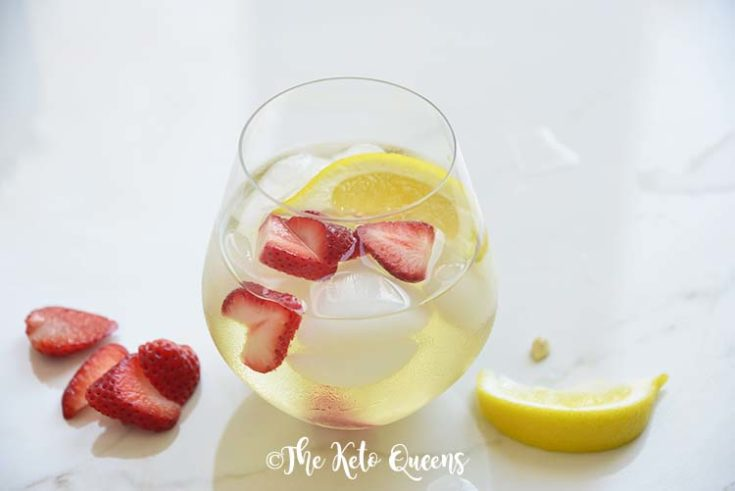 iced strawberry lemon tea in a seamless wine glass with lemon wedges
