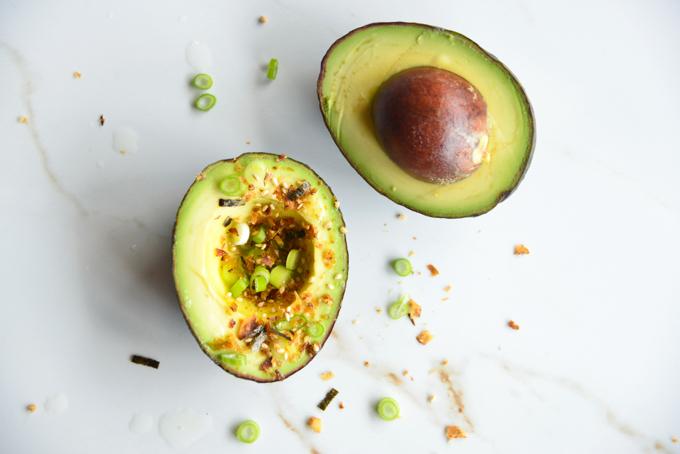 avocado split in half with seasoning on top