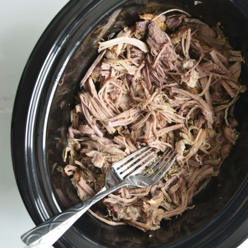 shredded pork in a black slow cooker with 2 forks