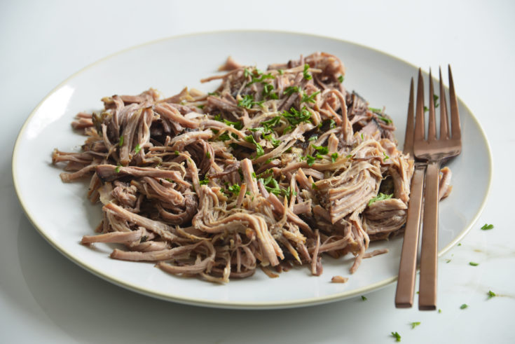 slow cooker pork butt shredded on a white plate with 2 forks