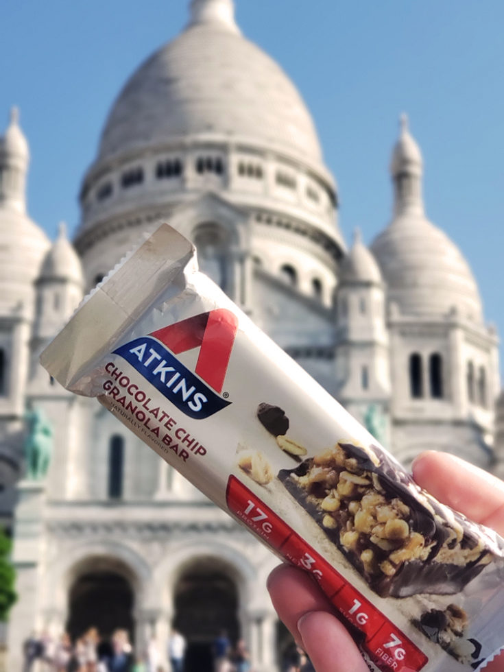 Atkins chocolate chip granola bar, a keto travel snack in front of acre couer in Paris
