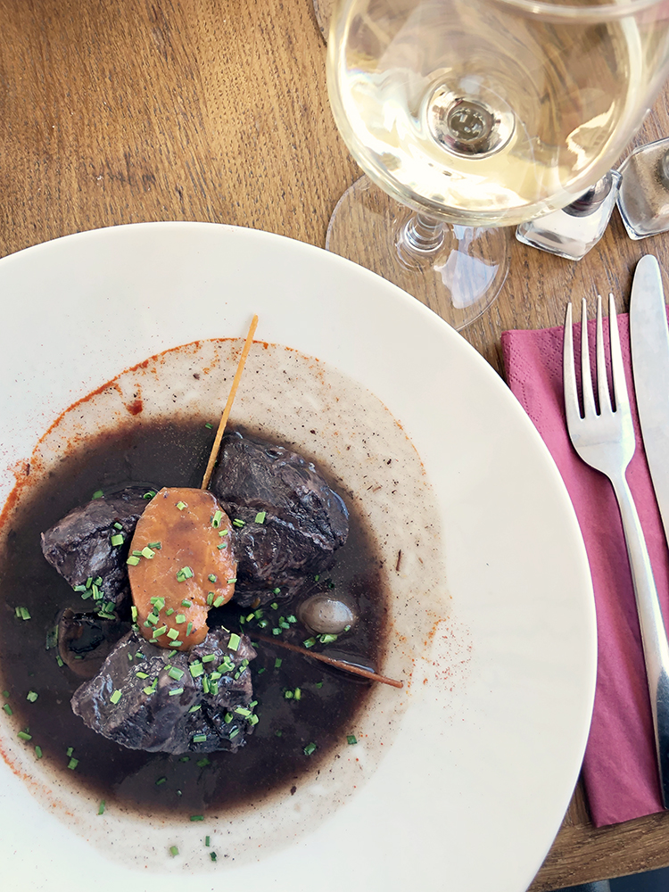 Beef Burgundy in White Bowl with Glass of Wine
