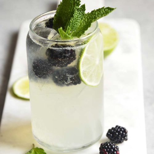 Blackberry Mojito Mocktail recipe in a clear glass garnished with mint, lime and blackberries