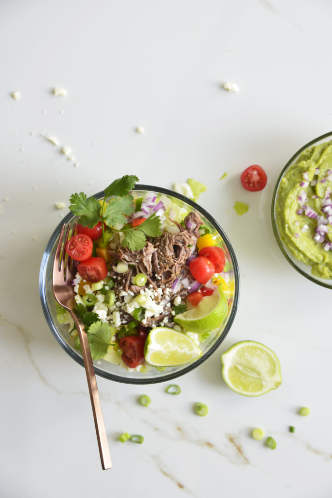 Shredded Beef Keto Taco Salad Recipe in a glass bowl with a fork on a white background with lime