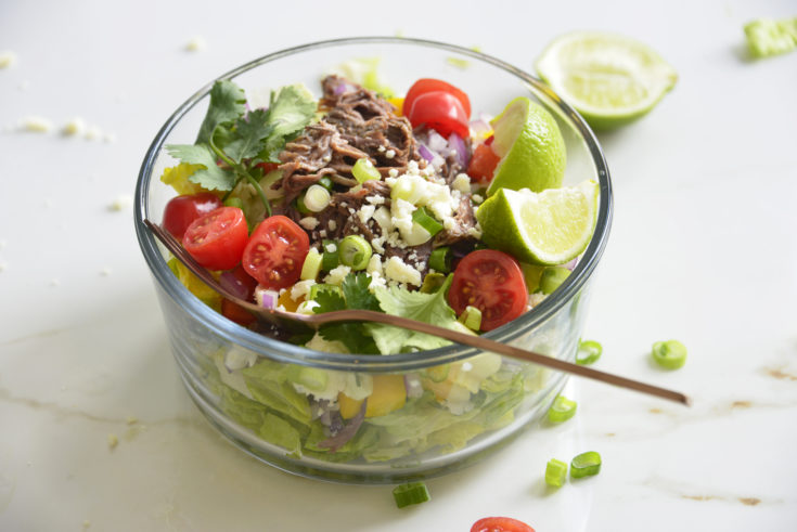 Shredded Beef Keto Taco Salad Recipe in a glass bowl on a white background with lime