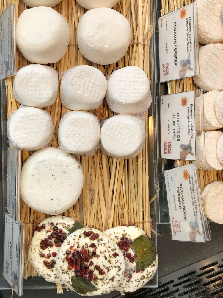 Top View of Different Types of Fromage au Lait Cru on Top of Straw in French Cheese Shop