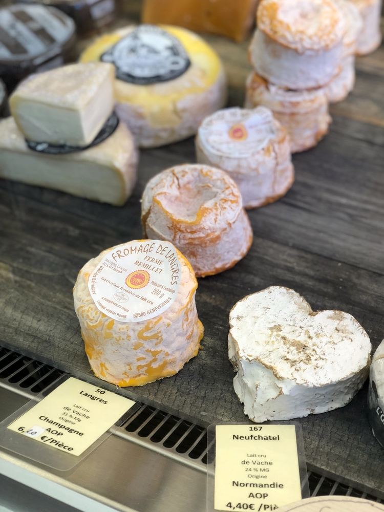 Langres and Neufchatel Cheeses on Wooden Shelf in Cheese Shop