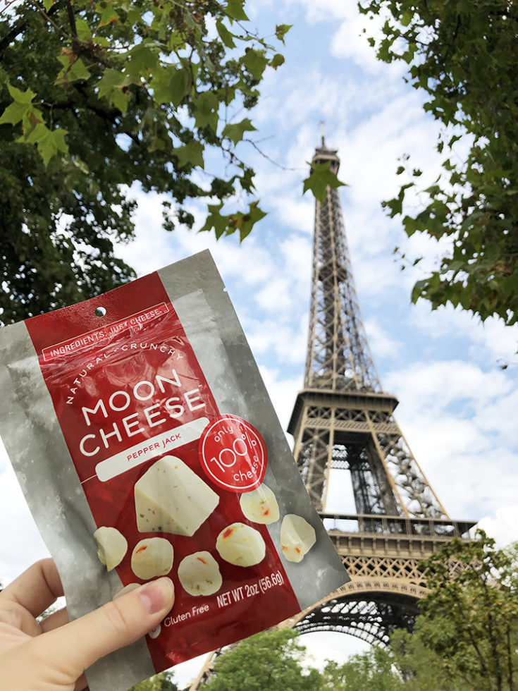 Moon Cheese pepper jack cheese a keto travel snack in front of the Eiffel Tower in Paris