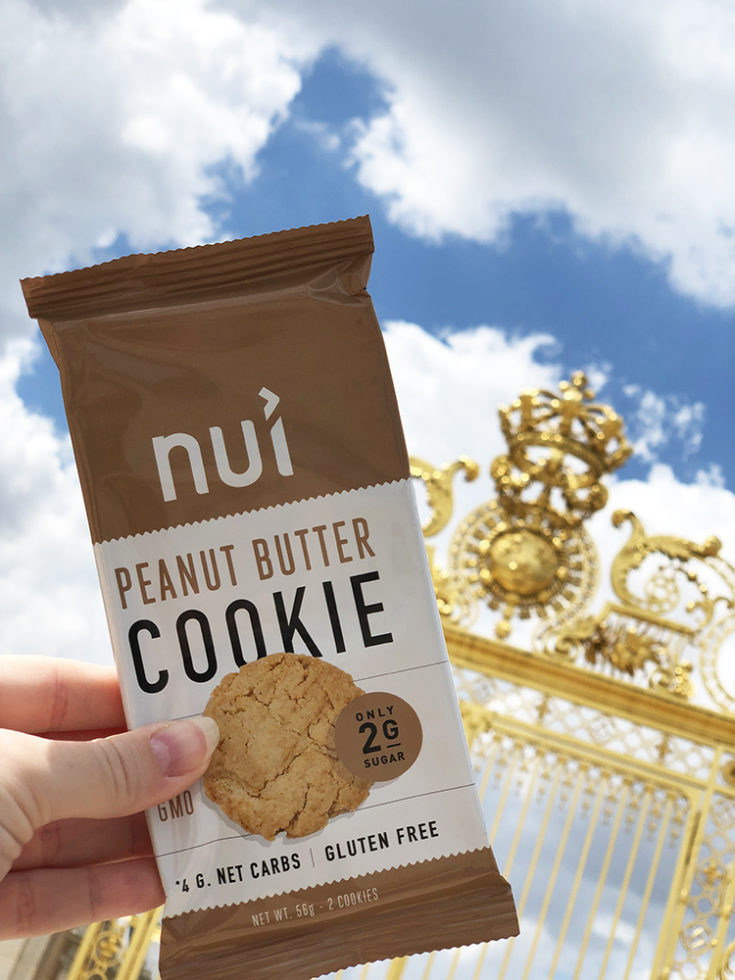 Nui Keto Cookie, a keto travel snack in front of the Golden gates of Versailles