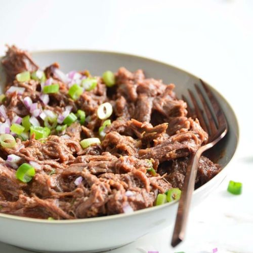 low carb pulled bbq beef recipe in a bowl with a fork on a white background