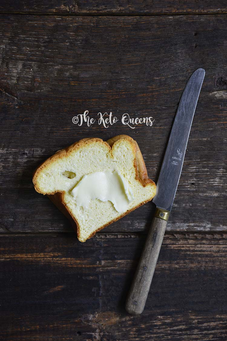Slice of White Bread with Butter on Dark Wooden Table