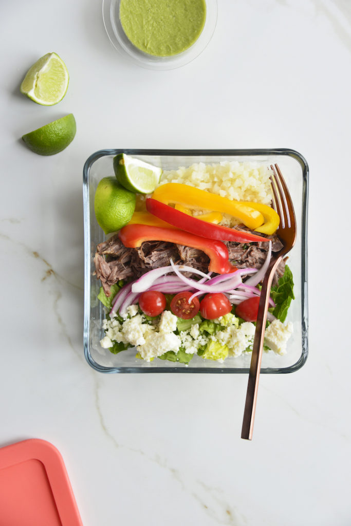 Prepared keto chipotle bowls in square glass meal prep containers with sliced limes and a fork