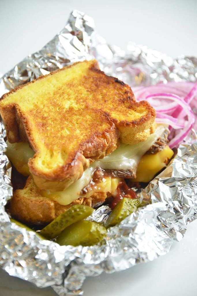 3 cheese keto grilled cheese sandwich on aluminum foil with pickles and red onions