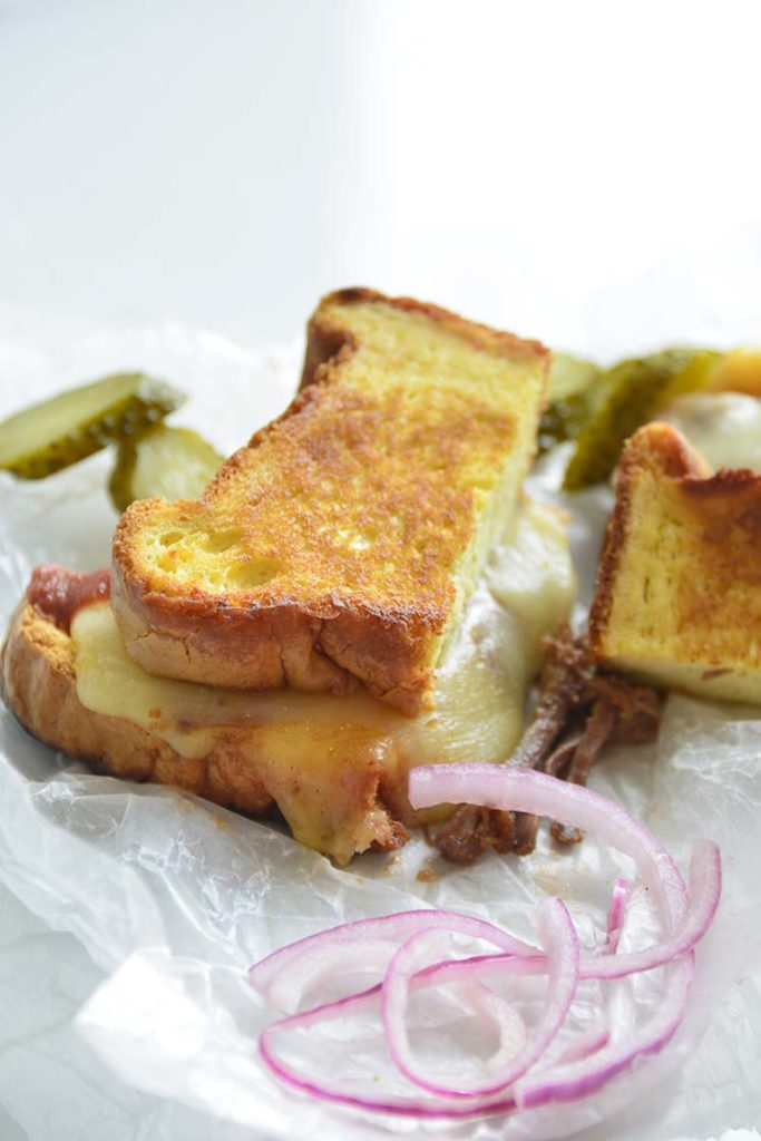 3 cheese keto grilled cheese sandwich on parchment paper with pickles and red onions