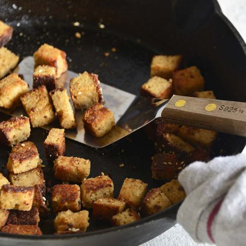 bacon croutons in a cast iron skillet with a wood handled spatula