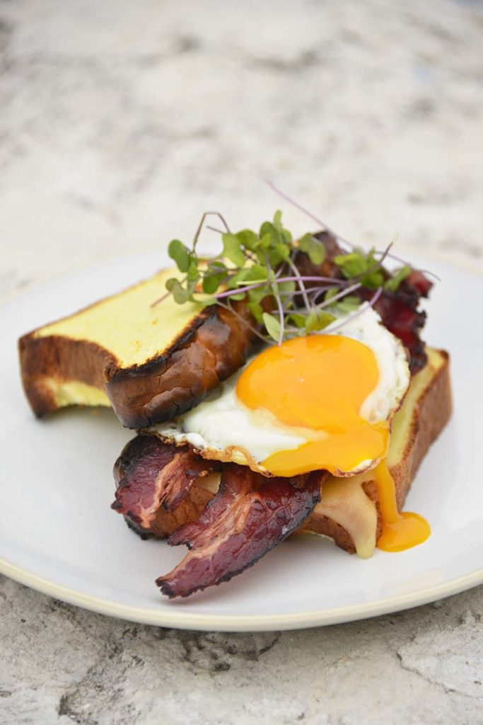 keto breakfast sandwich on a white plate topped with micro greens