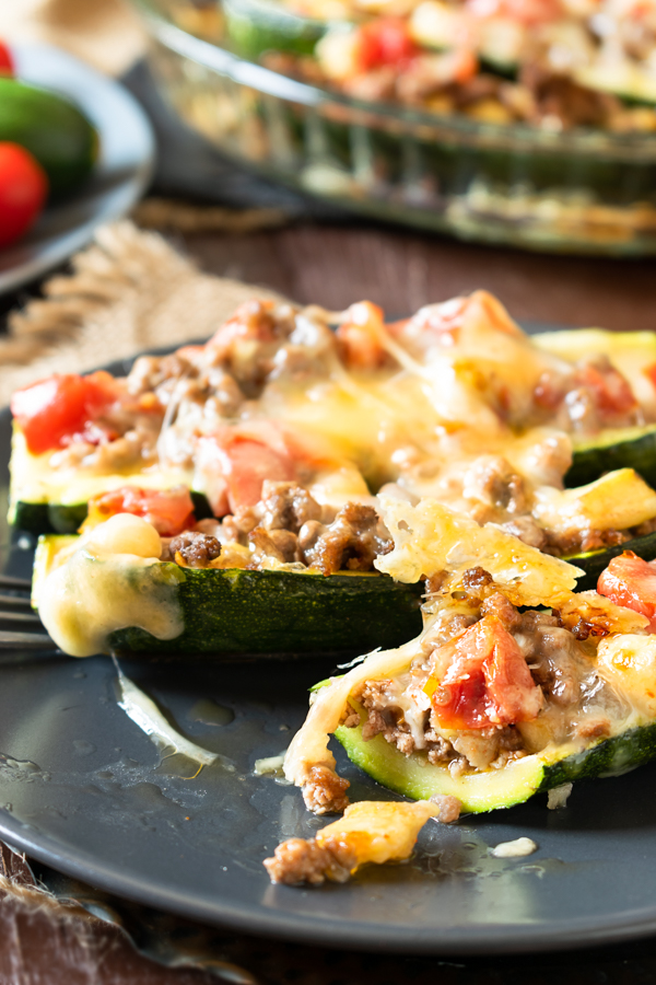 close up of slow cooker BBQ brisket stuffed zucchini boats on dark plates