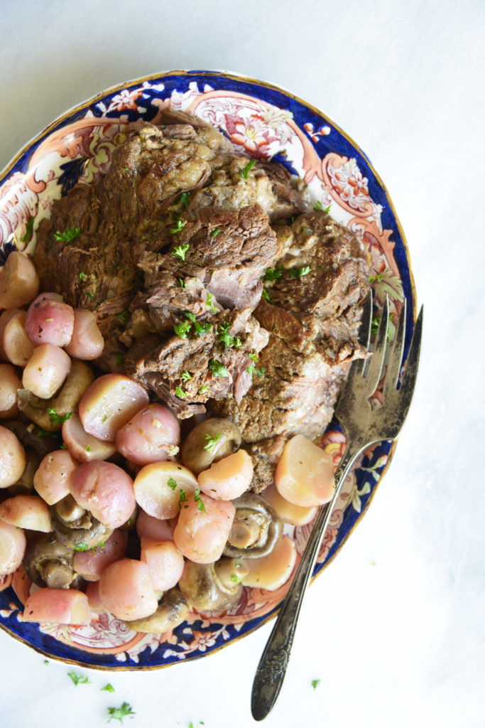 close up image instant pot pot roast with radishes on a white background