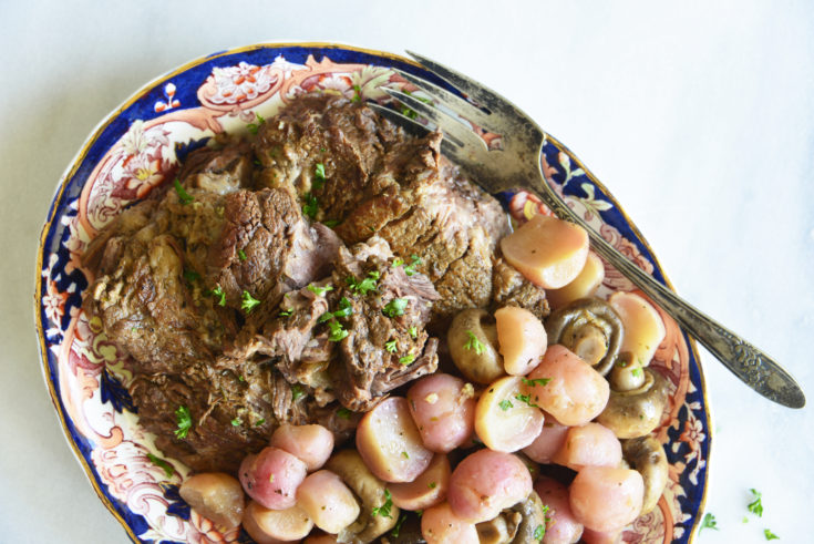 instant pot pot roast with radishes on a white background