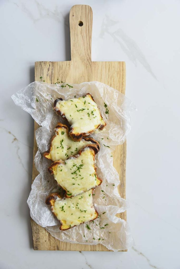 low carb Texas toast on a parchment paper and cutting board topped with parsley