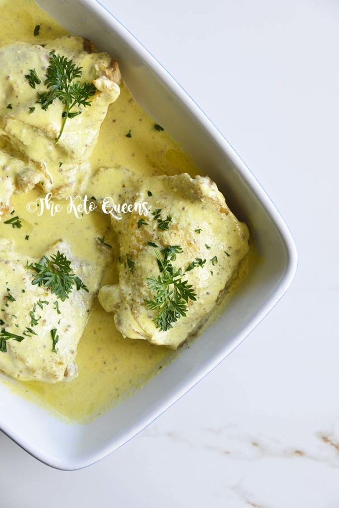 Roasted Chicken Thighs with Creamy Mustard Sauce in a blue and white casserole dish