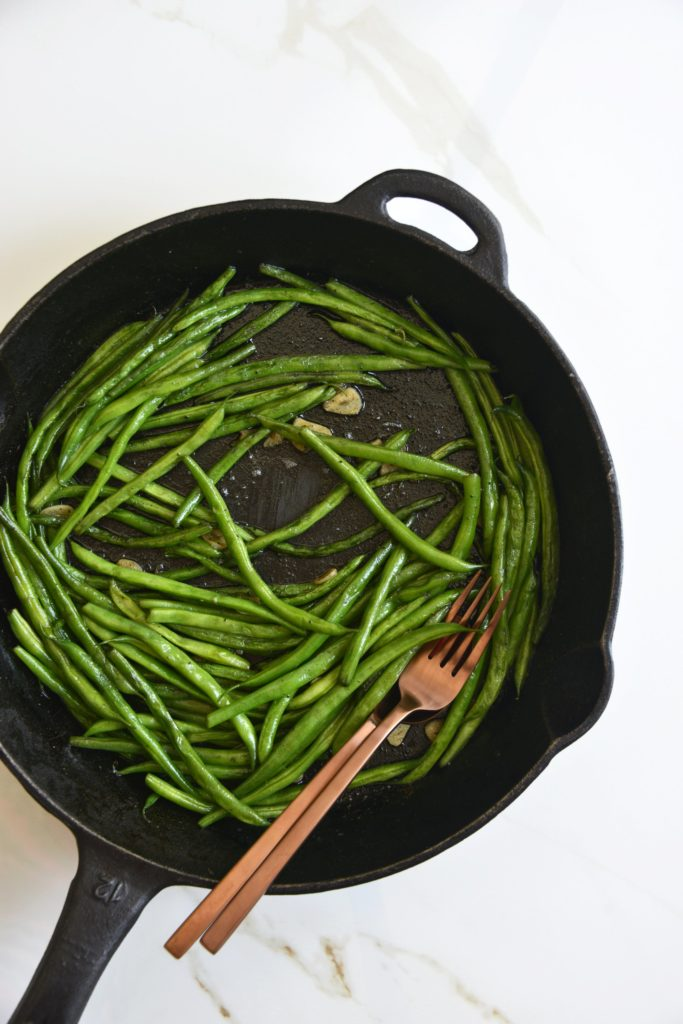 garlicky green beans cooked in a cast iron skillet