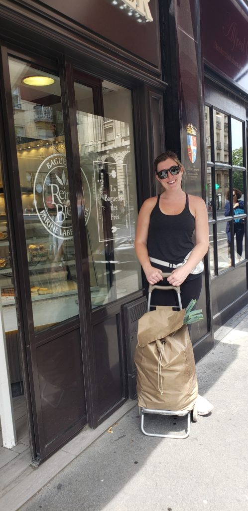 Lara pushing a basic full of groceries in paris
