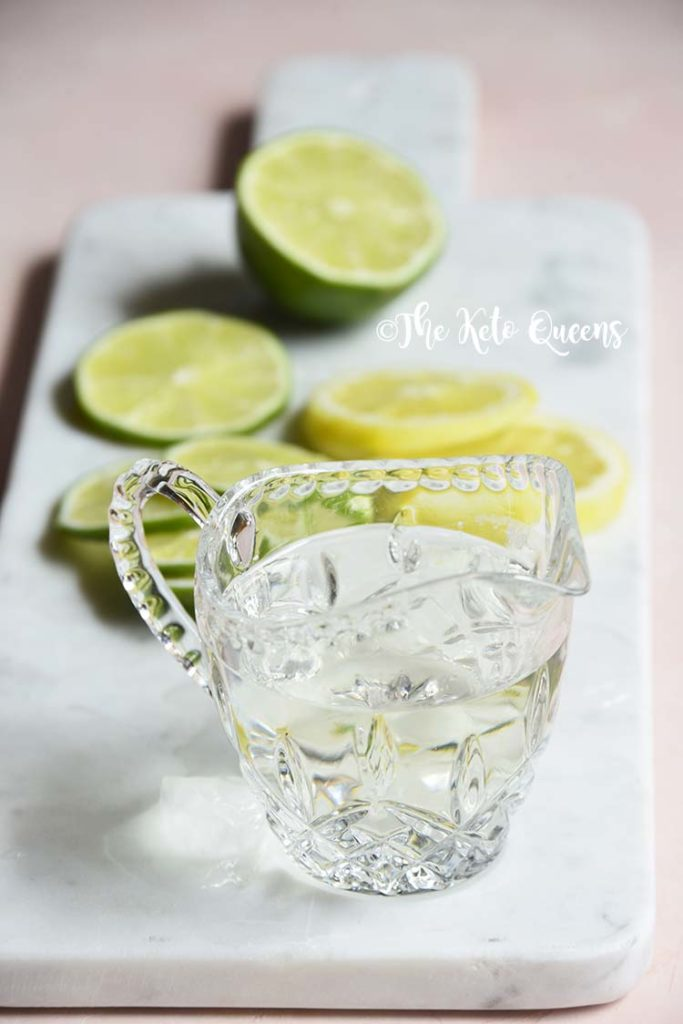 keto simple syrup in a glass with lemons and limes