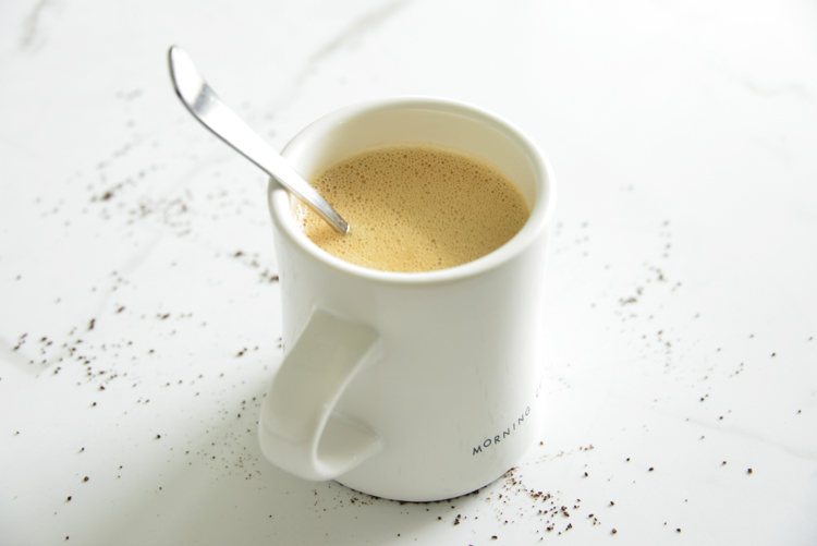 image of bulletproof coffee in a white mug with a spoon